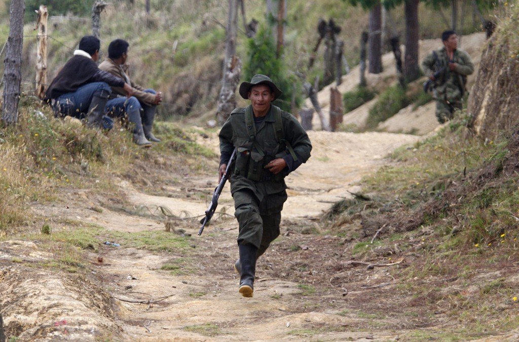 A member of the Revolutionary Armed Forces of Colombia (FARC) runs during a battle with the Colombian Army in the mountains of Jambalo, in the province of Cauca