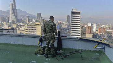 Un miembro de las Fuerzas Armadas, cumple labores de vigilancia, desde la terraza de un edificio en Bogotá. Foto: Efraín Herrera